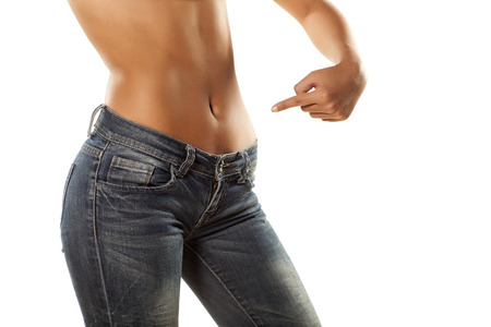 pretty girl with bare belly in tight jeans shows a finger on her stomach photo