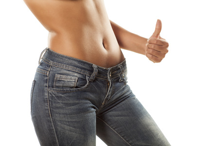 pretty girl with bare belly in tight jeans showing thumbs up photo