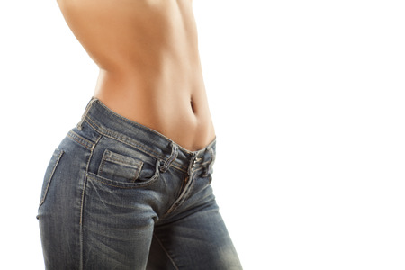 jolie fille avec le ventre nu dans des jeans serrés sur un fond blanc