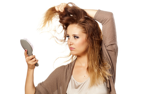 unhappy beautiful girl combs her hair and looking at the damaged ends photo