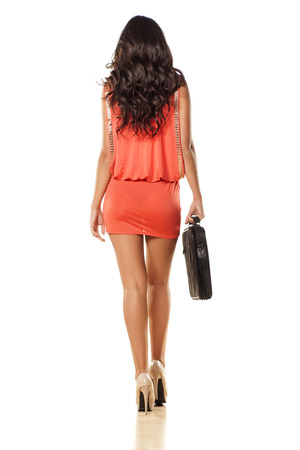 rear view of attractive and pretty girl in orange dress and laptop bag Stock Photo