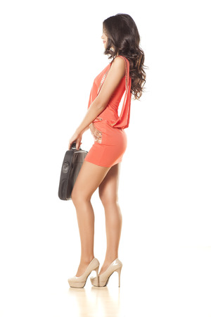 side view of attractive and pretty girl in orange dress and laptop bag photo