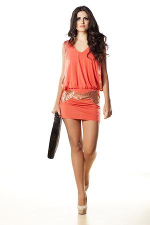 ropa casual: chica atractiva y bonita en traje de color naranja y una bolsa de ordenador portátil para caminar hacia ti Foto de archivo