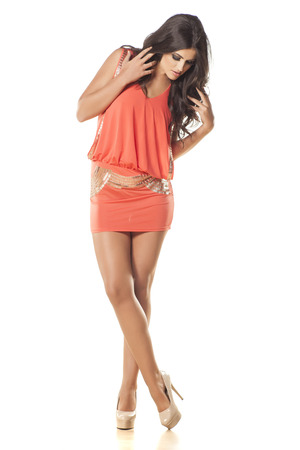 attractive and pretty girl in orange dress posing on white background photo