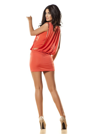 pretty girl in orange dress pointing a finger in the blank on white background photo