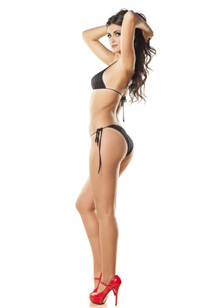 leg: side view of the attractive and beautiful girl in a black bikini