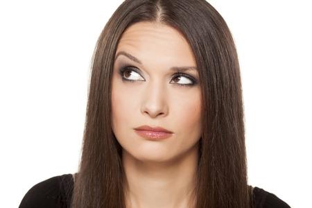 Portrait de la belle fille avec un geste douteux posant sur fond blanc Banque d'images - 24643393