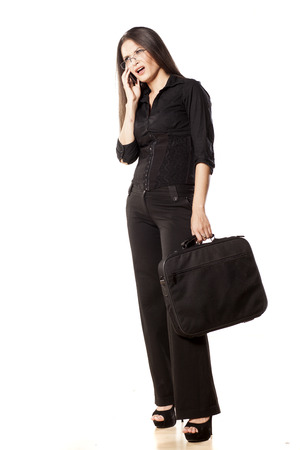 Sulky woman holding a laptop bag and talking on the phone photo
