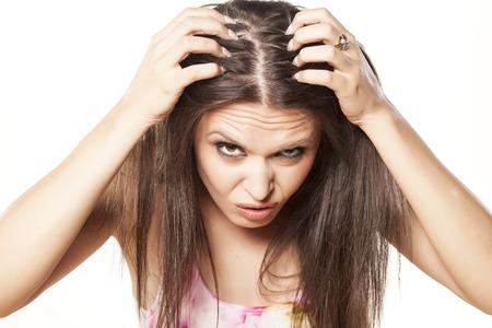 nervous girl looking in the mirror her scalp Standard-Bild