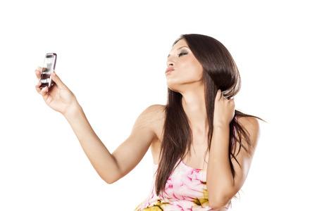 Belle fille de faire un auto-portrait avec son smartphone et faire un visage de canard Banque d'images - 24643348