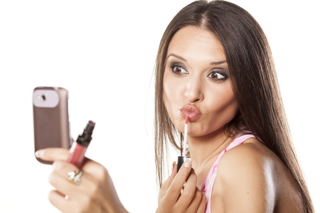 cute girl applied lipgloss to her lips and use a phone as a mirror Stock fotó - 24643353