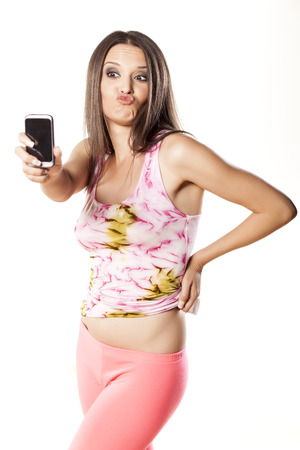 nice girl make a self-portrait with her smartphone and make a duck face