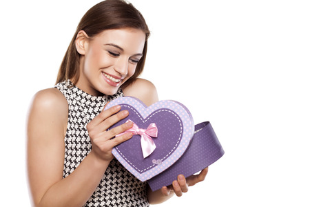 surprise box: beautiful smiling girl opening a gift box on a white background