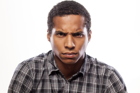 somber: somber dark-skinned young man poses with angry expression Stock Photo