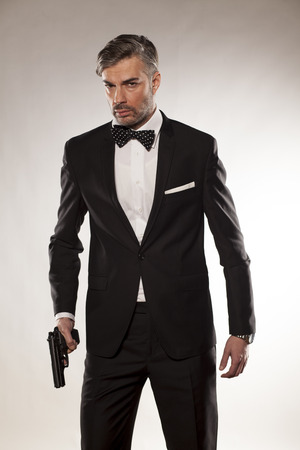 mature men: handsome man in a suit with a gun in his hand