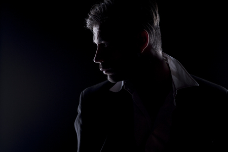 unnamed: Mens silhouette in the dark looking aside Stock Photo