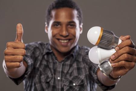 sparingly: African men holding different LED bulbs and showing thumbs up