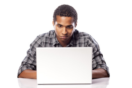dark-skinned young man looking uncertainly in front of his laptop