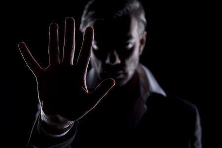 unknown men: Mens silhouette in the dark showing stop with a hand Stock Photo