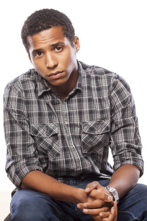 dark-skinned young man posing with a sad expression on white background