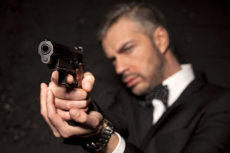 aiming: handsome man in a suit aiming with a gun