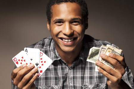 wade: african young man holds the winning combination of poker cards in one hand and wade of money in the other