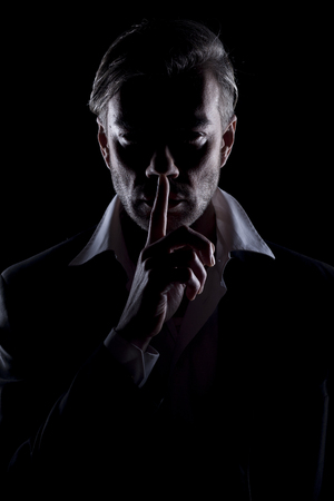 Men's silhouette in the dark showing silence gesture