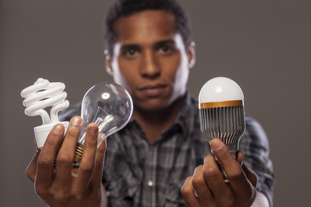 cree: man holding two of old generation light bulbs and one of the new generation of light bulbs