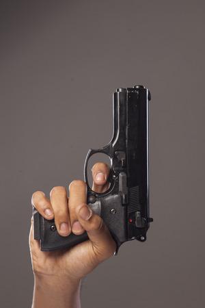 dark skinned: dark skinned mans hand with a gun