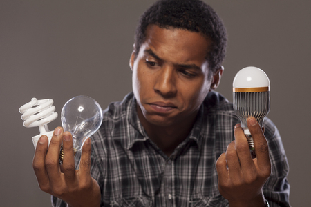 man holding two of old generation light bulbs and one of the new generation of light bulbs