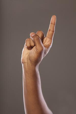 dark skinned: dark skinned hand pointing up on grey background