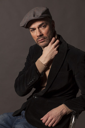 handsome pensive man in jacket and a cap in vintage style Stock Photo