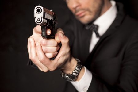 handsome man in a suit aiming with a gun