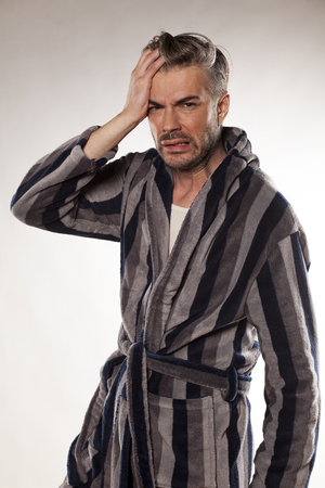 adult oops: handsome hungover man in a striped bathrobe Stock Photo