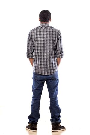 achteraanzicht van de jonge zwarte man met zijn handen in zijn zakken