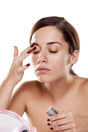 concealer: Beautiful young woman applying concealer around her eyes