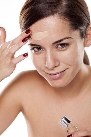 Beautiful young woman applying liquid base on her face Standard-Bild