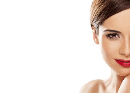 cuerpo femenino perfecto: mitad de la cara de una mujer sonriente joven hermosa en el fondo blanco