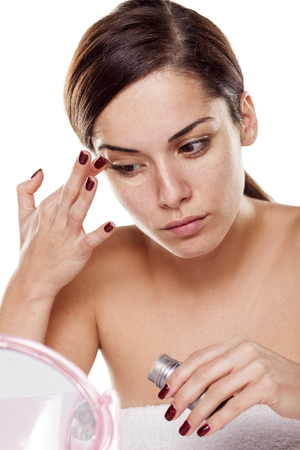 round eyes: Beautiful young woman applying concealer around her eyes