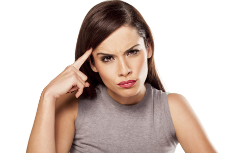 facial expression: angry pensive woman touching her forehead Stock Photo