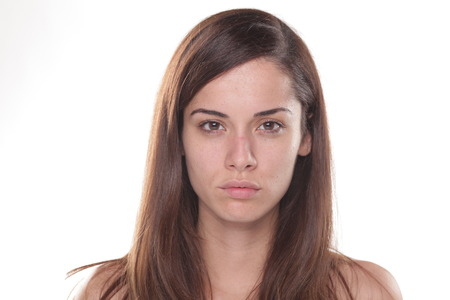 Poważne młoda piękna kobieta bez makijażu stwarzających na białym