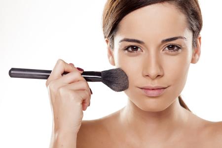 Beautiful young woman applying powder on her face Standard-Bild