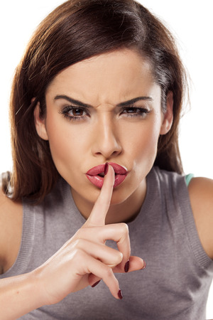 pretty girl holding a finger on her lips Standard-Bild