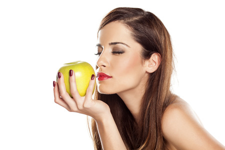 beautiful young woman smelling an apple
