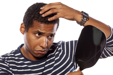 concerned dark-skinned young man settles himself in the mirror Standard-Bild