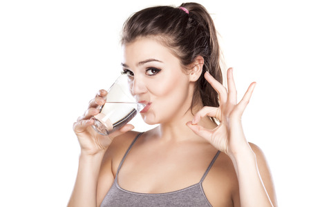 beautiful woman drinking water from a glass and showing sign for delicious Archivio Fotografico