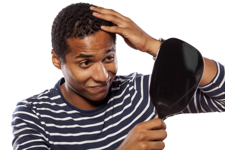 smiling dark-skinned young man settles himself in the mirror Stock Photo