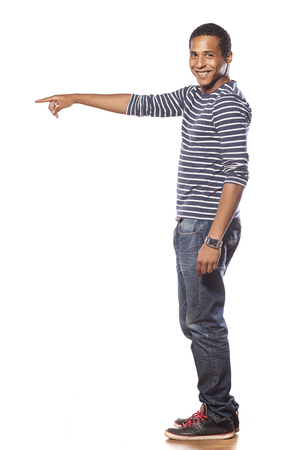 profil: smiling dark-skinned young man in jeans showing a direction Zdjęcie Seryjne