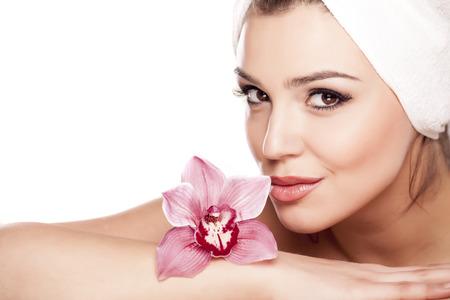 femme avec une serviette sur la tête appréciant le parfum d'une orchidée
