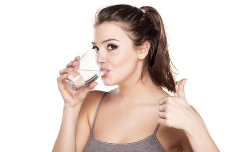 belle femme boit de l'eau à partir d'un verre et montrant le pouce en place